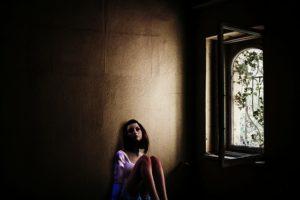 Traurige nachdenkliche Frau am Boden eines dunklen Raumes sitzend, beinahe wie in einem Gefängnis, Fenster mit Blumenranke. Symbol wie dem Ausgeliefertsein bei Liebeskummer